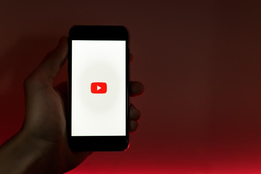 Uma mão segurando um celular com o app do YouTube aberto