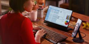 mulher usando o smartphone num monitor com teclado e mouse