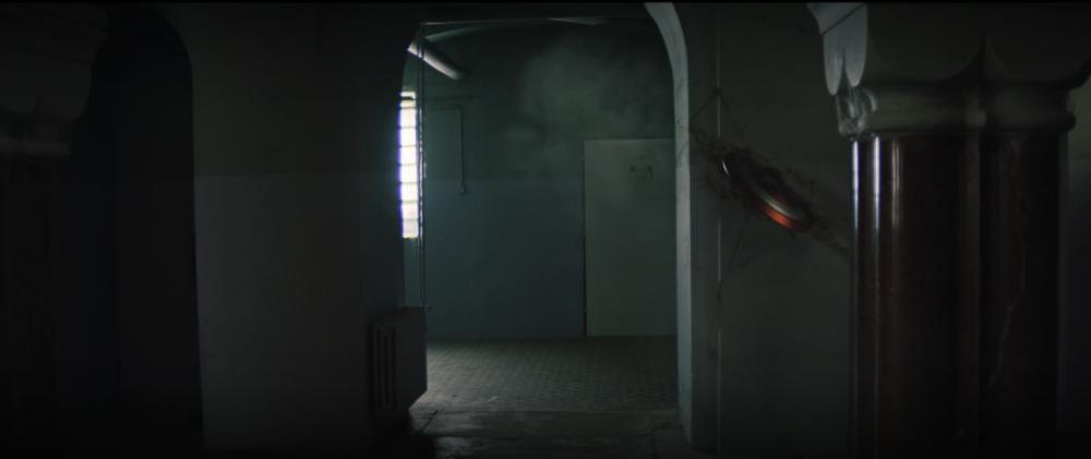John Walker usa sua super força para arremas o escudo em uma parede de concreto