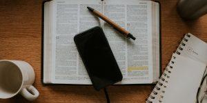 imagem de uma bíblia com um celular e uma caneta colocados em cima