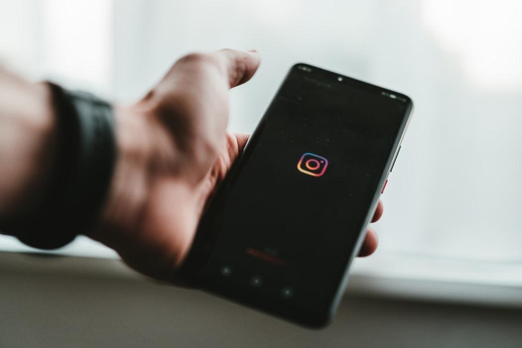 celular abrindo o aplicativo instagram, no modo escuro, com a logo num fundo preto