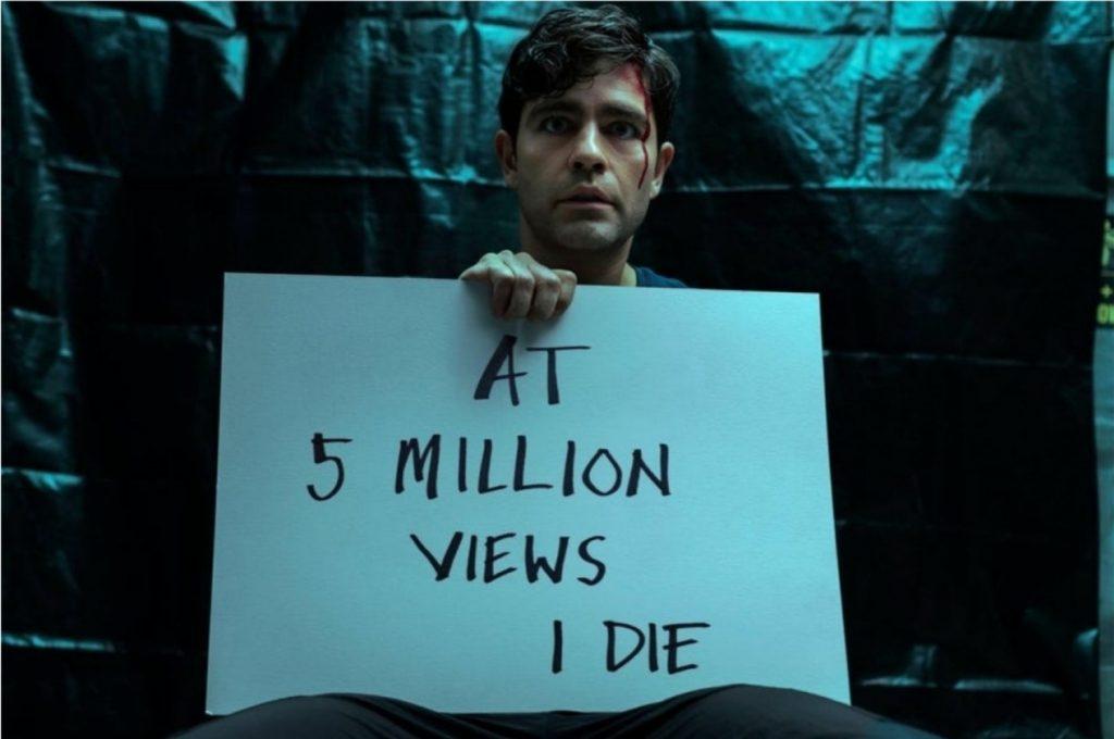 """Adrian Grenier como Nick Brewer na série Clickbait segurando uma placa escrita """"Aos 5 milhões de visualizações, eu morro"""" (Imagem: Divulgação/Netflix)"""